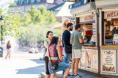 Två kvinna och två män som köper glass på en utomhus- glassstång Royaltyfri Foto