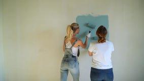 Två kvinnaarbetare som använder rullen för att måla väggarna i lägenheten eller huset Konstruktion, reparation och renovering lager videofilmer