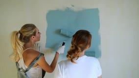 Två kvinnaarbetare som använder rullen för att måla väggarna i lägenheten eller huset Konstruktion, reparation och renovering arkivfilmer