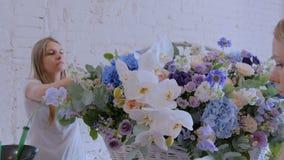 Två kvinnablomsterhandlare som gör den stora blom- korgen med blommor på blomsterhandeln stock video