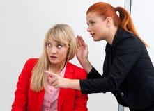 Två kvinnacolegues skvallrar i regeringsställning Arkivfoton