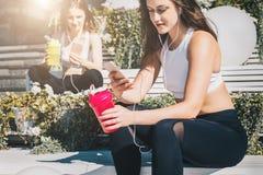 Två kvinnaidrottsman nen i sportkläder sitter på bänk, kopplar av efter sportar som utbildar, använder smartphones, lyssnar till  royaltyfria bilder