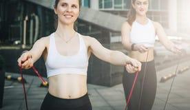 Två kvinnaidrottsman nen som hoppar på överhopprep i stadsgata Flickadrev utomhus Genomkörare sportar, sund livsstil Arkivfoton