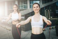 Två kvinnaidrottsman nen som hoppar på överhopprep i stadsgata Flickadrev utomhus Genomkörare sportar, sund livsstil Royaltyfria Foton