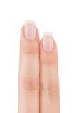 Två kvinnas fingrar med fransk manikyr. Royaltyfria Foton