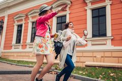 Två kvinnaturister som kör för att fånga en taxi i Odessa Lyckliga vänhandelsresande som skrattar, medan skynda sig upp royaltyfria bilder