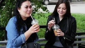 Två kvinnavänner att skvallra och diskutera på gatan, drinkcoctailar på en bänk arkivfilmer