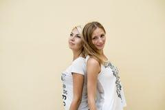Två kvinnavänner, den härliga brunetten och blont stående tillbaka som ska dras tillbaka, kopplar av tycker om Arkivbilder
