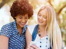 Två kvinnavänner parkerar in med mobiltelefonen Royaltyfri Foto