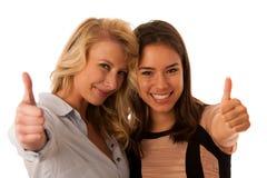 Två kvinnavänner som isoleras över den vita bakgrundsvisningen, tummar upp royaltyfria foton