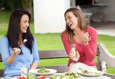 Två kvinnavänner som sitter utanför i trädgårds- ha lunch Royaltyfri Bild