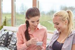 Två kvinnavänner som talar hållande kaffekoppar Royaltyfri Fotografi