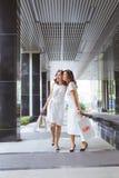 Två kvinnavänner som tillsammans shoppar och talar royaltyfri fotografi