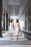 Två kvinnavänner som tillsammans shoppar och talar royaltyfri bild