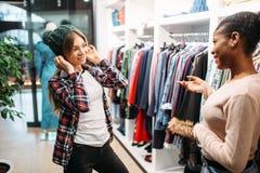 Två kvinnlig som köper kläder i, shoppar, shopping arkivfoton