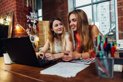 Två kvinnliga bloggers som har en vänlig konversation som diskuterar nya idéer som framme sitter av datoren hemma med royaltyfria foton