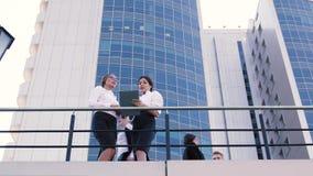 Två kvinnliga coworkers som utomhus talar under lunchtid och en man som kommer ut ur affärsmitten och talar på arkivfilmer