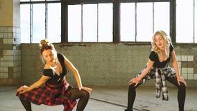 Två kvinnliga dansare värms upp före praktik i gamla fabriker arkivfilmer