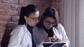 Två kvinnliga doktorer ser till och med medicinska anmärkningar i en mapp och konsulterar på diagnos Intelligent yrkesmässig sjuk arkivfilmer