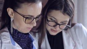 Två kvinnliga doktorer ser till och med medicinska anmärkningar i en mapp och konsulterar på diagnos Intelligent yrkesmässig sjuk stock video
