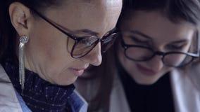 Två kvinnliga doktorer ser till och med medicinska anmärkningar i en mapp och konsulterar på diagnos Intelligent yrkesmässig sjuk lager videofilmer