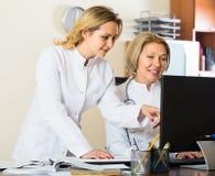 Två kvinnliga doktorer som tillsammans arbetar Fotografering för Bildbyråer