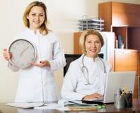 Två kvinnliga doktorer som visar tid i klocka fotografering för bildbyråer