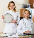 Två kvinnliga doktorer som visar tid i klocka arkivbild