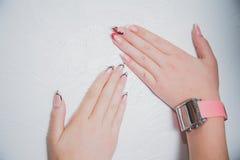 Två kvinnliga händer med spikar polermedel, skönhetmode Royaltyfria Bilder