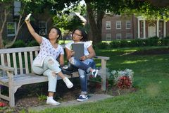 Två kvinnliga högskolestudenter på universitetsområde med ryggsäckar och böcker Royaltyfria Bilder