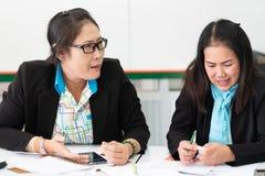 Två kvinnliga kollegor för asiatisk mitt- ålder som tillsammans arbetar och gör en presentaion i regeringsställning royaltyfri bild