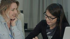 Två kvinnliga kollegor som diskuterar lyckligt nytt projekt i kontoret arkivfoton