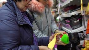 Två kvinnliga kunder väljer köktillbehör i maskinvarulagret