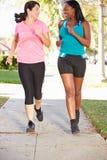 Två kvinnliga löpare som övar på den förorts- gatan arkivfoton