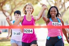 Två kvinnliga löpare som tillsammans avslutar loppet Arkivbilder