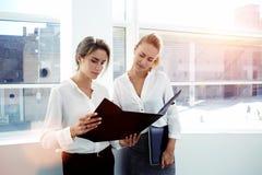 Två kvinnliga ledare som analyserar dokument, når att ha arbetat på handlagblocket, medan de som står i modern kontorsinre, arkivbild