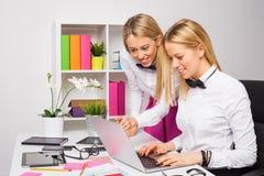 Två kvinnliga medarbetare som arbetar som ett lag på bärbara datorn Royaltyfri Fotografi