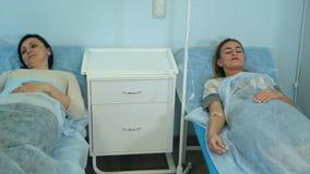 Två kvinnliga patienter på droppander som ligger på sängar i sjukhussalen som kontrolleras av den manliga doktorn stock video