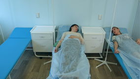 Två kvinnliga patienter som ligger i sjukhussängar på droppandesamtal arkivfilmer