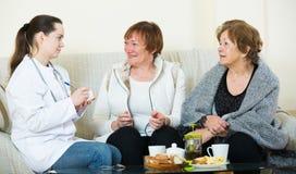Två kvinnliga pensionärer som diskuterar hälsoproblem med doktorn Arkivbilder