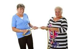 Två kvinnliga pensionärer som drar på ett rep Royaltyfri Bild