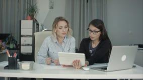 Två kvinnliga professionell som använder den digitala minnestavlan, medan arbeta på skrivbordet arkivbilder