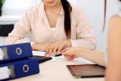 Två kvinnliga revisorer som räknar på räknemaskininkomst för avslutning för skattform, räcker closeupen Skattemyndigheten Fotografering för Bildbyråer