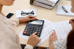 Två kvinnliga revisorer som räknar på räknemaskininkomst för avslutning för skattform, räcker closeupen Skattemyndigheten Arkivbilder