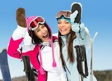Två kvinnliga skidåkarevänner med händer upp royaltyfri foto