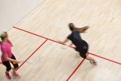 Två kvinnliga squashspelare i snabb handling på en squashdomstol Royaltyfria Bilder