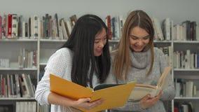 Två kvinnliga studenter jämför information bokar itu på arkivet stock video