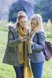Två kvinnliga studenter som använder deras mobiltelefoner fotografering för bildbyråer