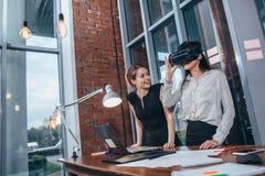 Två kvinnliga studenter som spelar en 3d, spelar i VR-exponeringsglas som har ett avbrott efter en kurs i klassrumet Arkivfoton