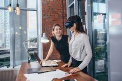 Två kvinnliga studenter som spelar en 3d, spelar i VR-exponeringsglas som har ett avbrott efter en kurs i klassrumet Royaltyfri Foto